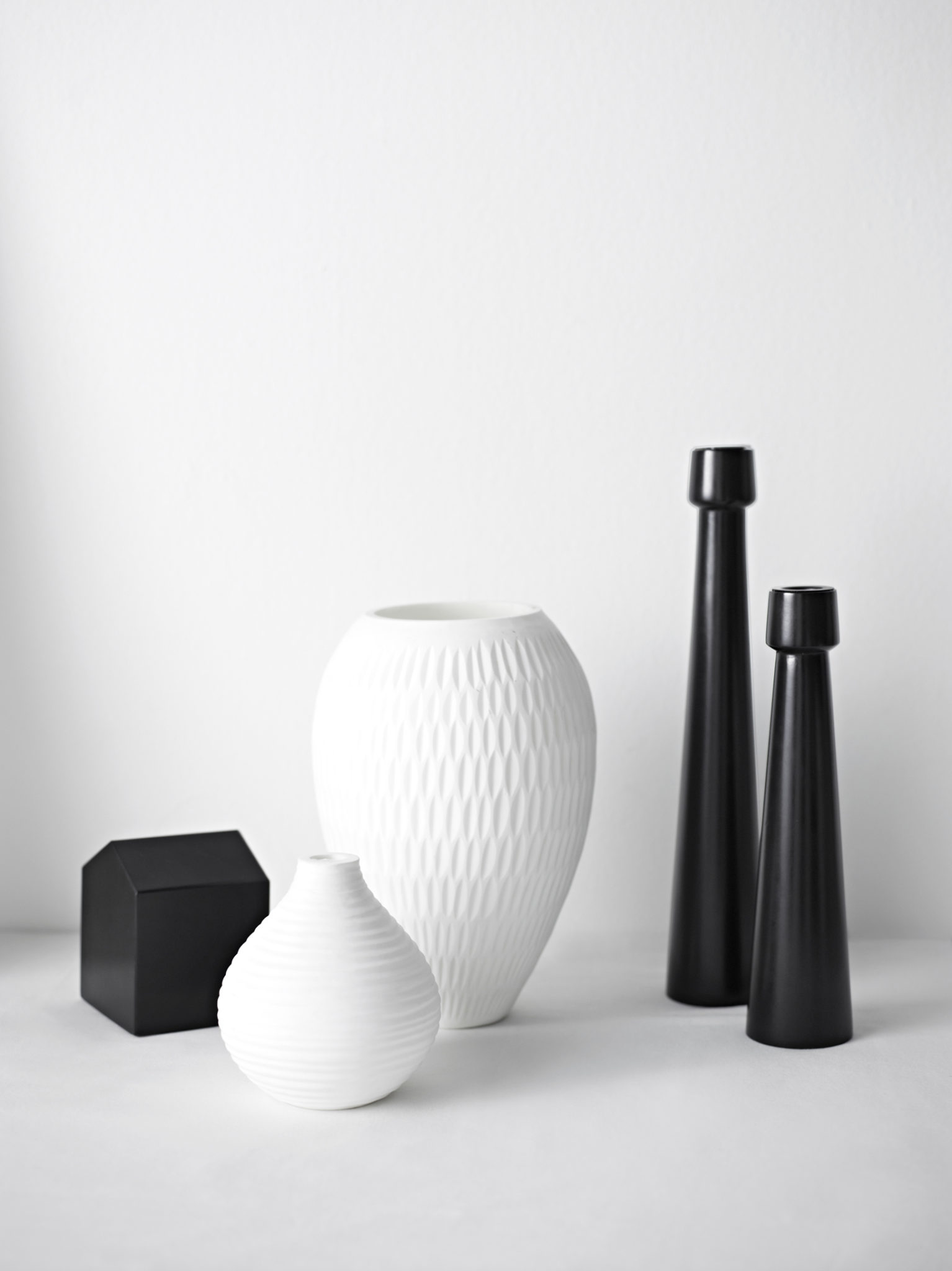 I love the texture of the white vessels paired with the high gloss of the black candlesticks