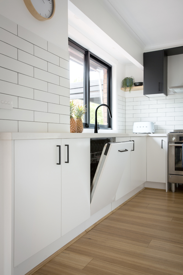 AFTER In the new design, the dishwasher has been integrated into the cabinetry, hiding it away neatly under the sink.