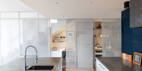 Perforated screens conceal under-stair storage in the kitchen