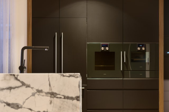 The concealed fridge sits next to Gaggenau appliances