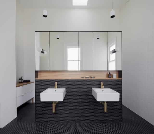 The ensuite is divided by a wall that conceals the toilet and shower behind