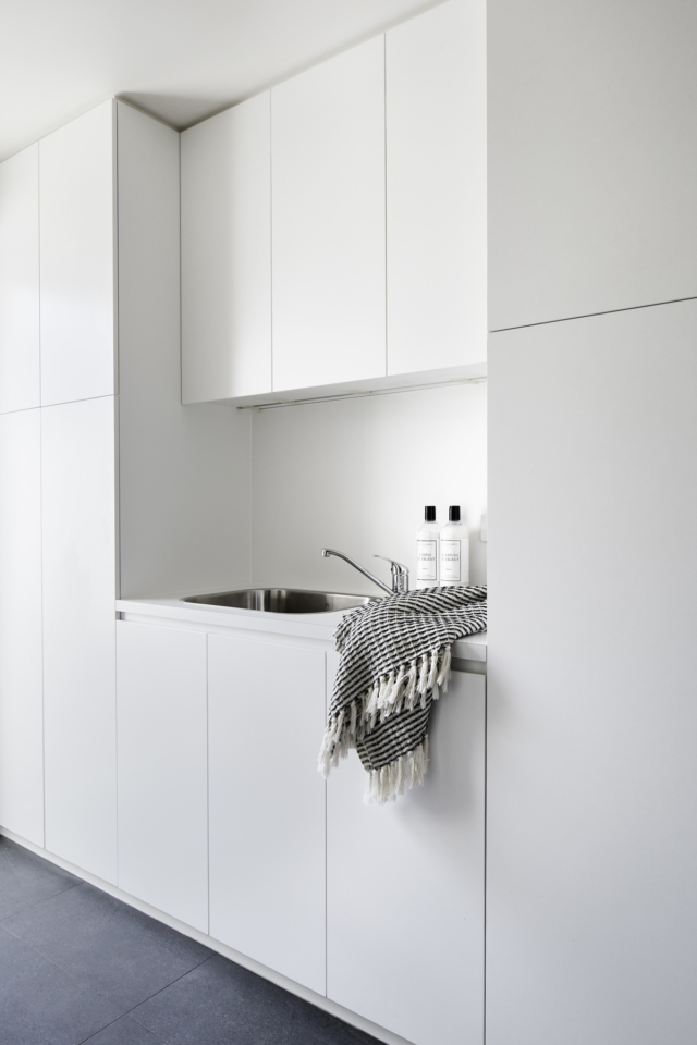 The laundry is concealed behind the blue kitchen