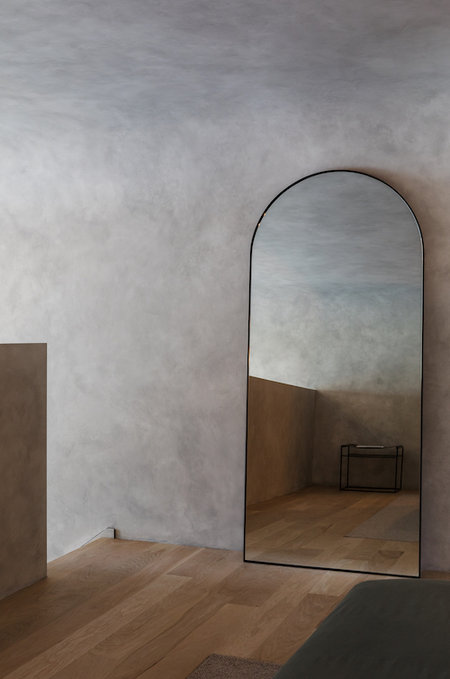 Curves are repeated in the bedroom with this mirror