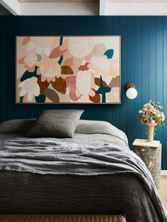 A Kimmy Hogan piece pops on the dark bedroom wall